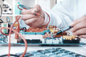 Electronics repair service, hands of female tech reparing an electronic circuit